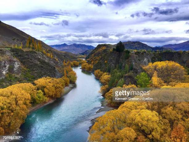 scenic view of river amidst trees growing on mountains against sky - arrowtown stock pictures, royalty-free photos & images