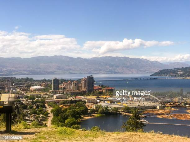 scenic view of river and buildings against sky - kelowna stock pictures, royalty-free photos & images