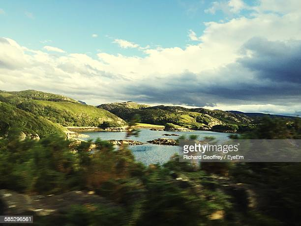 Scenic View Of River And Hill Against Cloudy Sky