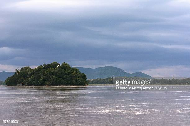 scenic view of river and mountains against cloudy sky - guwahati stock pictures, royalty-free photos & images