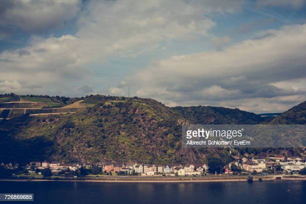 scenic view of river and mountains against cloudy sky - albrecht schlotter stock photos and pictures