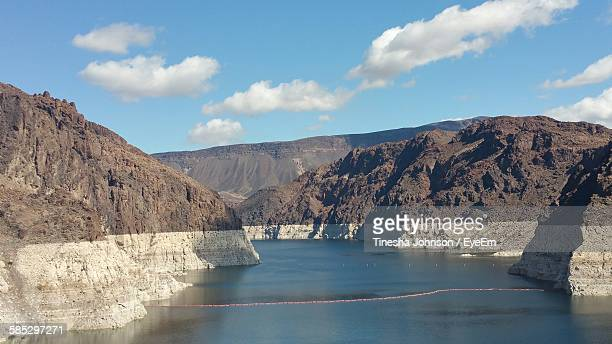 scenic view of river and rocky mountains against sky - johnson stockfoto's en -beelden