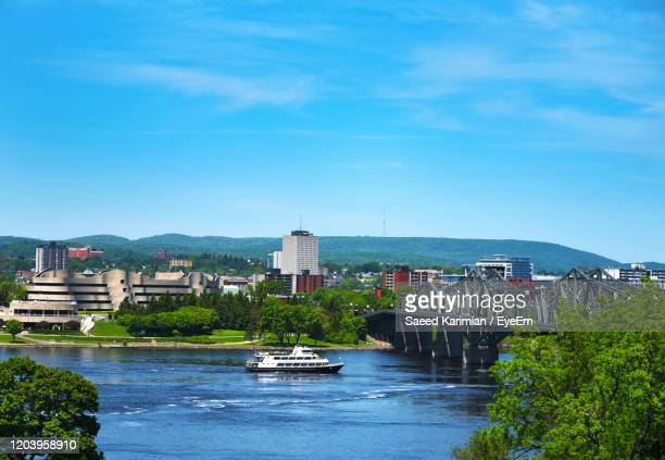 scenic view of river by buildings against blue sky - gatineau stock pictures, royalty-free photos & images
