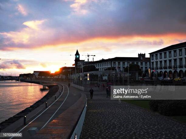scenic view of river by buildings against sky at sunset - ponta delgada fotografías e imágenes de stock