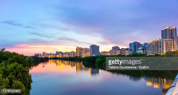 scenic view of river by buildings against sky during sunset - sanya stock pictures, royalty-free photos & images