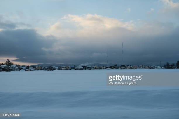 Scenic View Of River By Buildings Against Sky During Winter