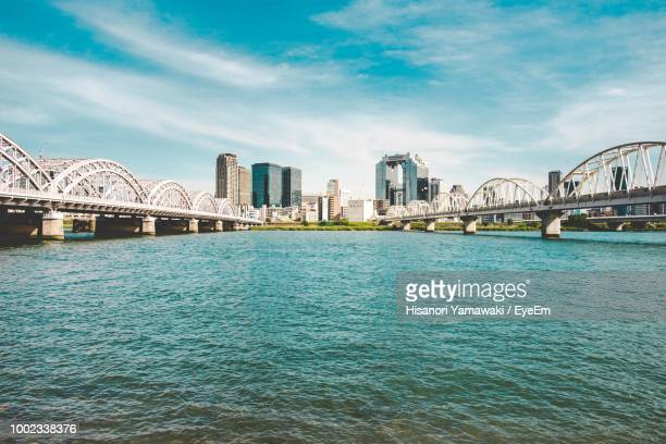 scenic view of river by buildings against sky - 大阪 ストックフォトと画像