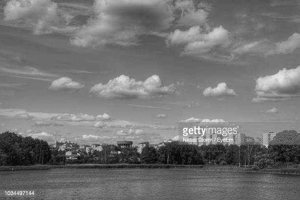 scenic view of river by buildings against sky - ソルナ ストックフォトと画像