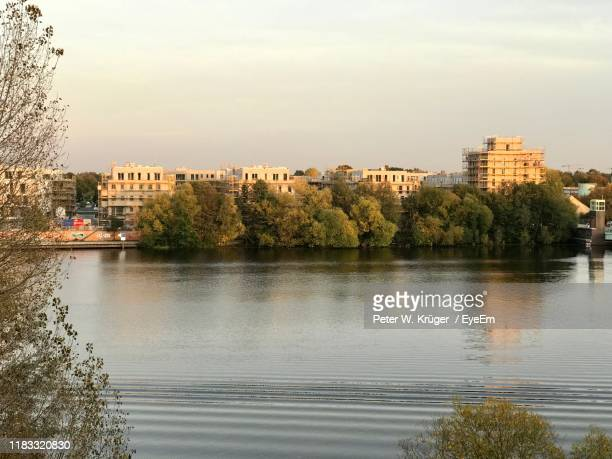 scenic view of river by buildings against sky - spandau stock pictures, royalty-free photos & images