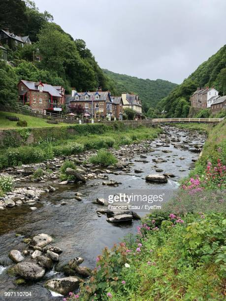 scenic view of river by buildings against sky - devon stock pictures, royalty-free photos & images