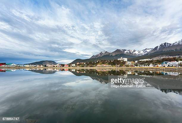 Scenic View Of River By Buildings And Mountains Against Cloudy Sky