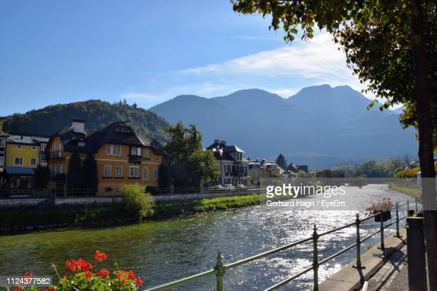 Scenic View Of River By Buildings And Mountains Against Sky