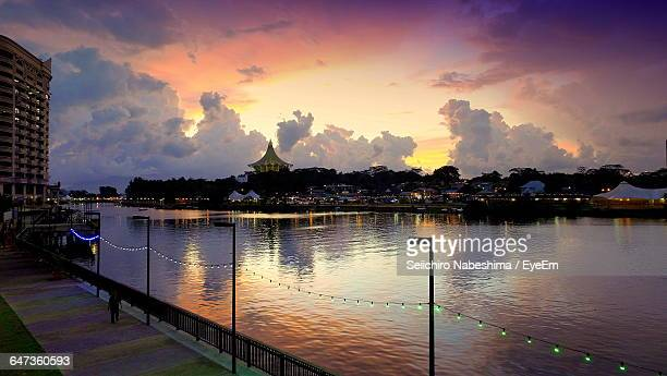 Scenic View Of River By Buildings In City During Sunset