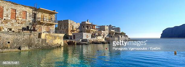 scenic view of river by houses against clear blue sky - vgenopoulos stock pictures, royalty-free photos & images