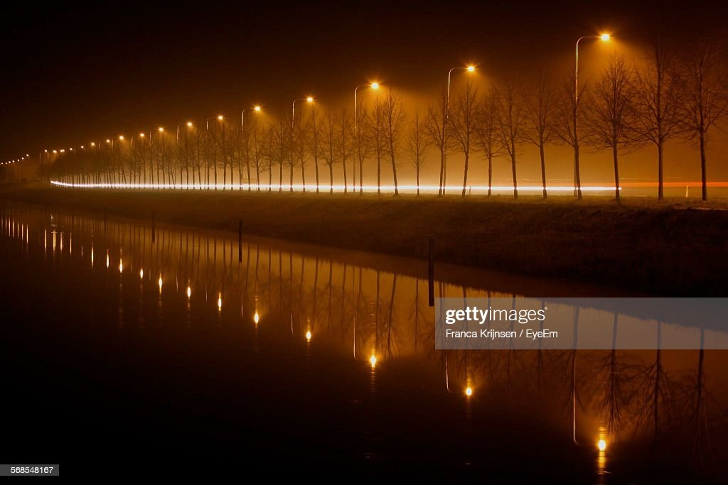 Scenic View Of River By Illuminated Street Light At Night : Stock Photo
