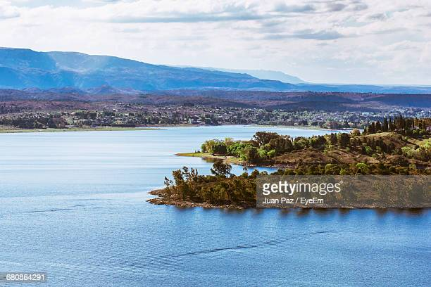 scenic view of river by mountain against sky - cordoba argentina stock photos and pictures