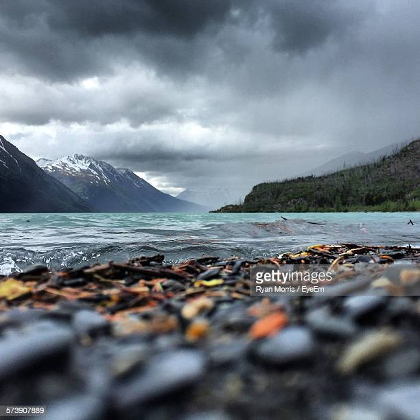Scenic View Of River By Mountains Against Cloudy Sky