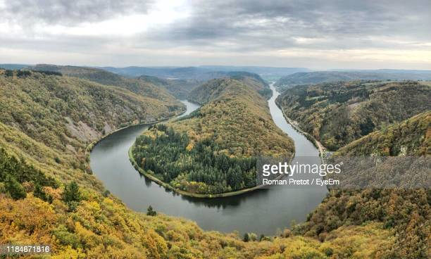 scenic view of river by mountains against sky - roman pretot stock-fotos und bilder