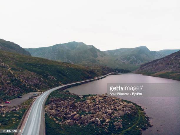 scenic view of river by mountains against sky - wales stock pictures, royalty-free photos & images