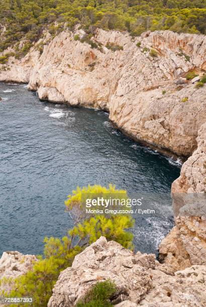 scenic view of river by rock formation - monika gregussova stock pictures, royalty-free photos & images