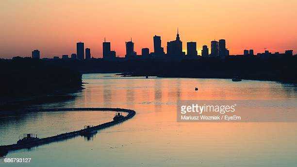 Scenic View Of River By Silhouette Buildings During Sunset