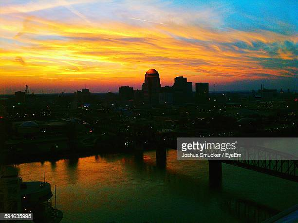 scenic view of river by silhouette cityscape against sky during sunset - baton rouge stock pictures, royalty-free photos & images