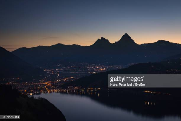 scenic view of river by silhouette mountains against sky at sunset - schwyz stock pictures, royalty-free photos & images
