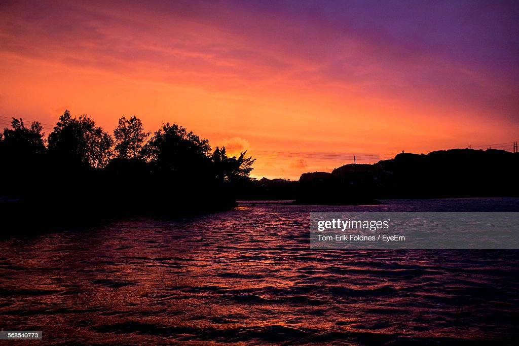 Scenic View Of River By Silhouette Trees Against Cloudy Sky : Stock Photo