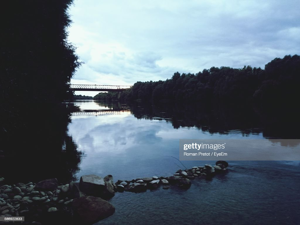 Scenic View Of River By Silhouette Trees Against Sky At Dusk : Stock-Foto