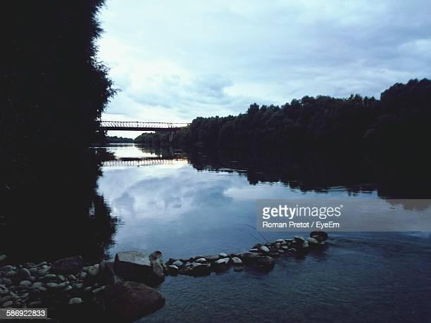 scenic view of river by silhouette trees against sky at dusk - roman pretot stock-fotos und bilder