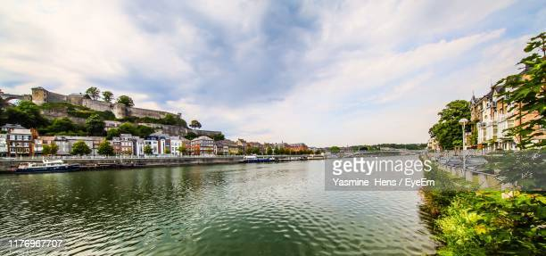 scenic view of river by town against sky - ナミュール州 ストックフォトと画像
