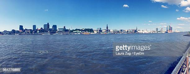 Scenic View Of River In Front Of Cityscape Against Blue Sky