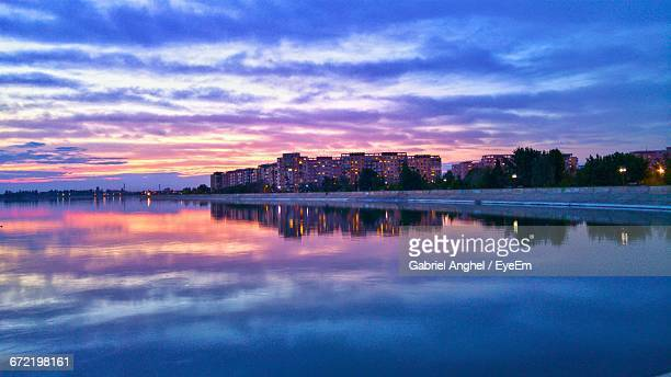 Scenic View Of River With Clouds Reflections At Sunset