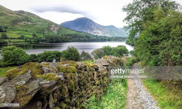 scenic view of river with mountains in background - cockermouth photos et images de collection