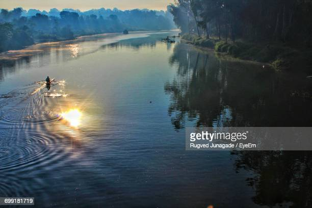 Scenic View Of River With Reflection Of Sun During Sunrise