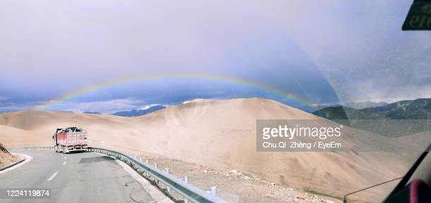 scenic view of road against rainbow in sky - rainbow mountains china stock-fotos und bilder