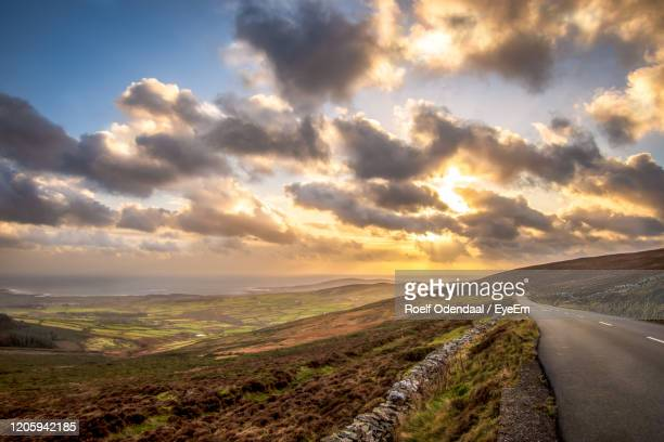 scenic view of road against sky during sunset - isle of man stock pictures, royalty-free photos & images