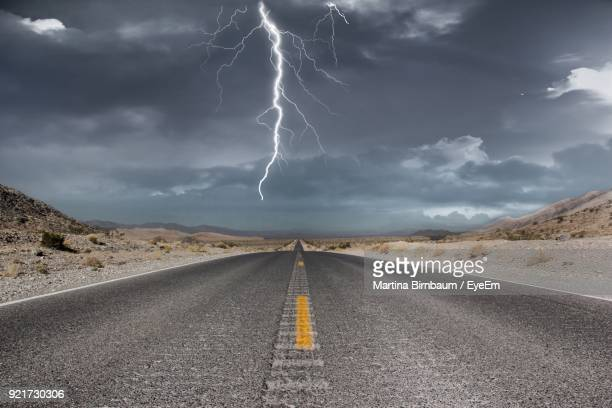 scenic view of road against storm clouds - death valley photos et images de collection