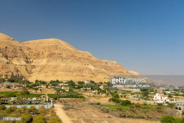 scenic view of road amidst buildings against clear sky - jericho stock photos and pictures