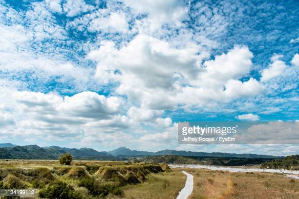scenic view of road amidst field against sky - jeffrey roque stock photos and pictures