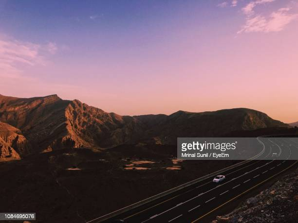 scenic view of road and mountains against sky during sunset - ras al khaimah stock pictures, royalty-free photos & images