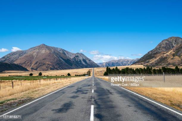 scenic view of road by mountains against blue sky, oxford, new zealand - images stock pictures, royalty-free photos & images