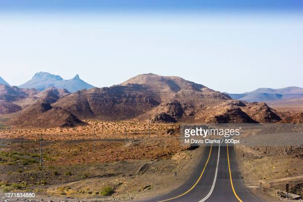 scenic view of road by mountains against clear sky, tabuk, saudi arabia - images stock pictures, royalty-free photos & images