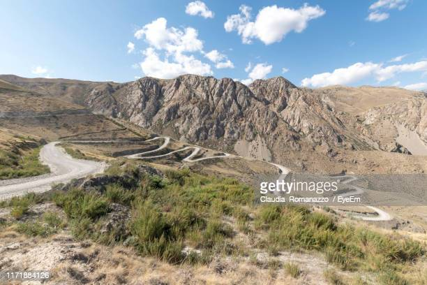 scenic view of road by mountains against sky - claudia romanazzo foto e immagini stock