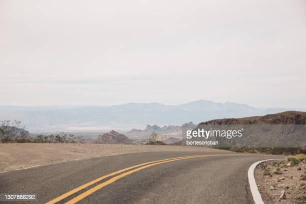 scenic view of road by mountains against sky - bortes fotografías e imágenes de stock