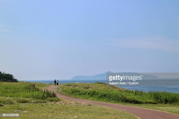 Scenic View Of Road By Sea Against Clear Sky