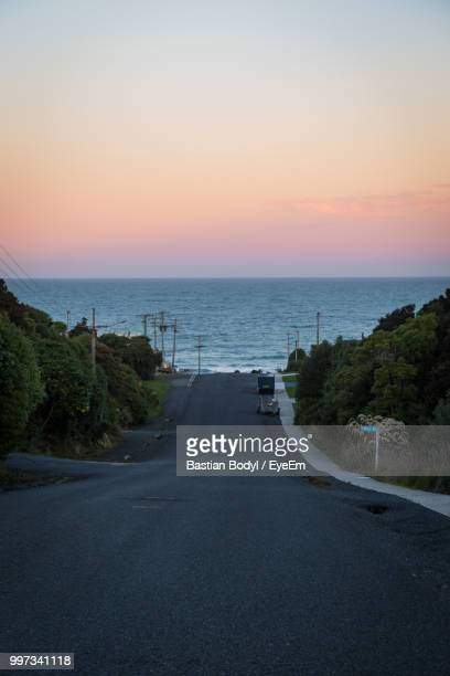 Scenic View Of Road By Sea Against Sky During Sunset