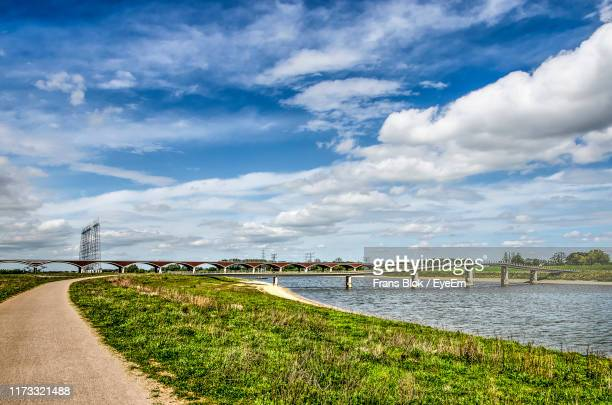 scenic view of road by sea against sky - gelderland stock pictures, royalty-free photos & images