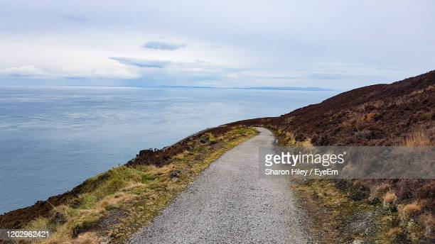 scenic view of road by sea against sky - rocky coastline stock pictures, royalty-free photos & images