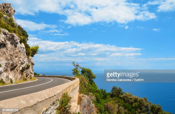 scenic view of road by sea against sky - südeuropa stock-fotos und bilder